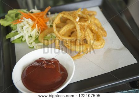 plate of deep fried onion rings with catchup / selective focus