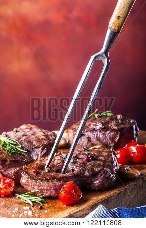 Steak. Grill beef steak. Portions thick beef juicy sirloin steaks on grill pan or old wooden board.