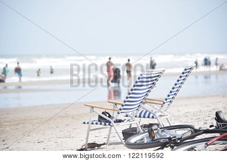 Two empty chairs on beach with bicycle, with people strolling the shoreline in the background.