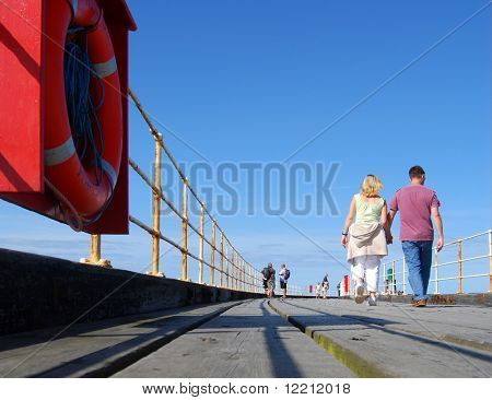 Young couple enjoy strolling on Whitby pier on sunny day. Whitby, North Yorkshire, UK.