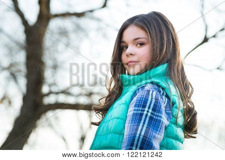 Cute fun and stylish caucasian tween girl outside tree in background