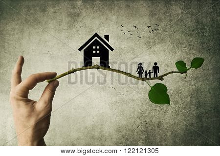 Human hand holding a tree branch with silhouettes of house and family. The concept of a happy family. Eco life