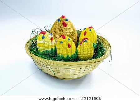 A brood of crochet chickens in a wicker basket.