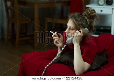 Photo of lonely girl with cigarette and telephone lying