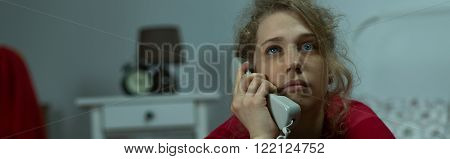 Panorama of depressed lonely woman talking on phone