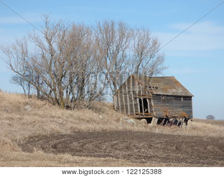 A old building with a crumbling foundation on a abandoned farmstead