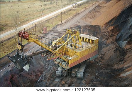 The big dredge digs the earth in a quarry