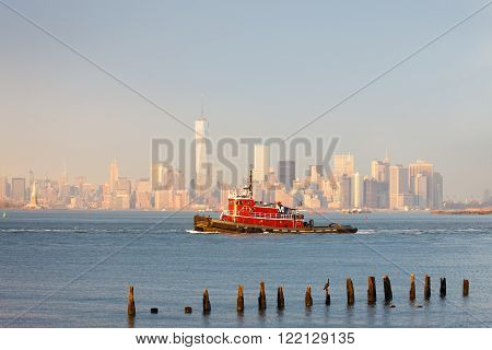 Tugboat in New York Harbor in afternoon soft winter light with the Financial District of Lower Manhattan in background.New York City. ** Note: Soft Focus at 100%, best at smaller sizes