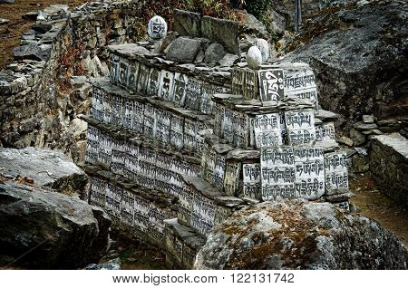 Stone with the Buddhist mantras lying on the way to Everest Base Camp in Himalayas Nepal
