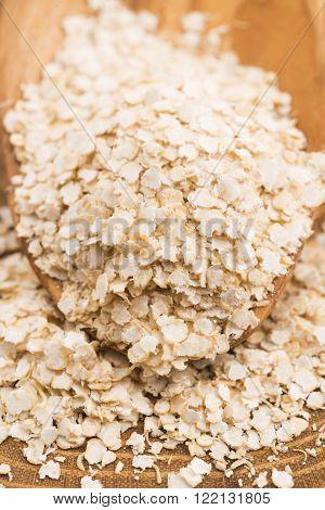 Quinoa flakes on wooden spoon, macro view