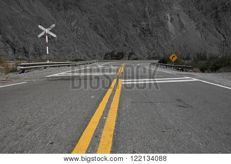 Winding empty road crossing a railroad in northern Argentina