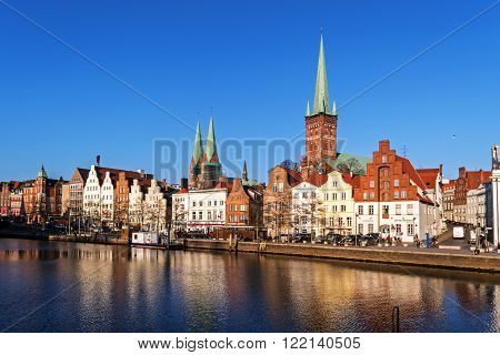 Luebeck, Germany - march 16, 2016: Historic old town of Luebeck, Germany at the pier of the river trave tourism attraction with brick architecture churches and cathedrals and the urban street life Europe North Germany, Luebeck, March 16, 2016: