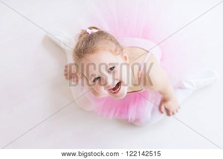Little ballerina girl in a pink tutu. Cute child dancing classical ballet in white studio. Children dance. Young dancer in a class. Preschool kid sitting on hardwood floor. Copy space for your text.
