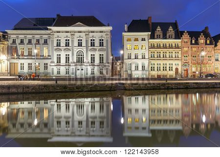 Picturesque medieval building on the quay Korenlei with reflections in Ghent town at night, Belgium