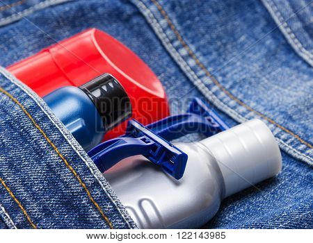 Antiperspirant deodorant, shaving cream, aftershave lotion and disposable razors in jeans pocket. Basic skin care cosmetic products and accessories for men. Toiletry and cosmetic travel kit