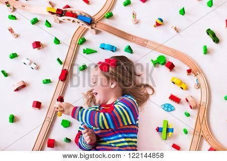 Child playing with wooden train rails and cars. Toy railroad for kids. Educational toys for preschool and kindergarten children. Little girl at daycare. View from above kid playing on the floor.