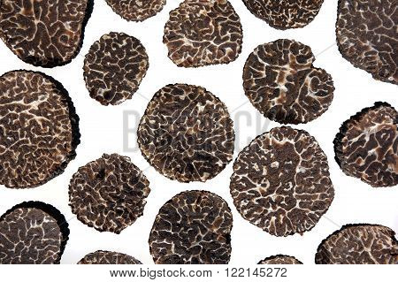 sliced black truffles isolated on white background