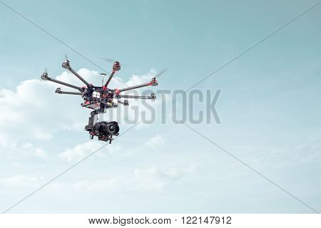 Copter shoots in flight on a background of beautiful blue sky. RC aircraft in the sky.