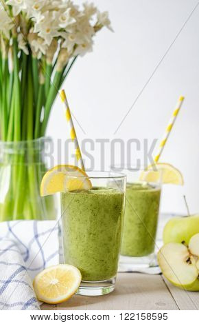Healthy green smoothie with spinach and apple in a glass on wood