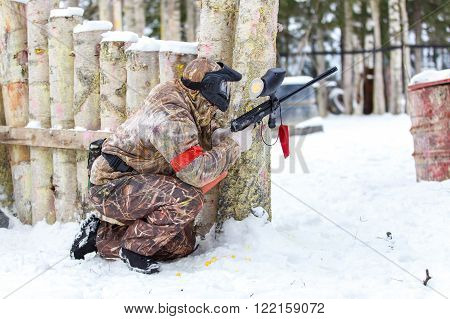 Paintball game in winter. Cool shooter behind fortification. poster