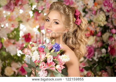 Beautiful fashion model. Sensual bride. Woman with wedding hair and make up. Sweet flowers background.  Blue eyes. Natural manicure. Beauty spring girl with bouquet of flowers in hands and hair