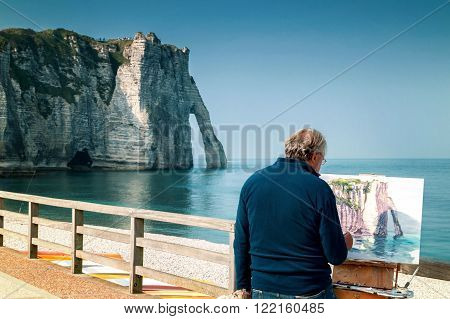 Etretat, France - September 23rd, 2014: Painter paints the white cliffs of Etretat with the famous Natural Arch La Porte d`Aval, Alabaster Coast, Normandy,