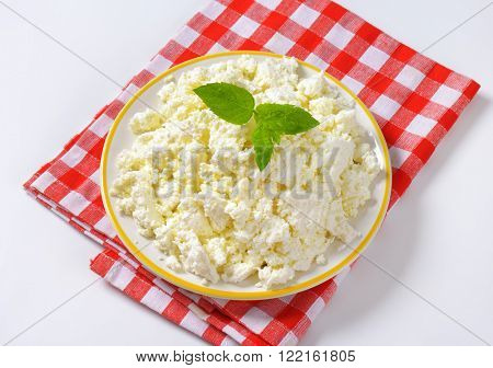 plate of crumbly white cheese on checkered dishtowel