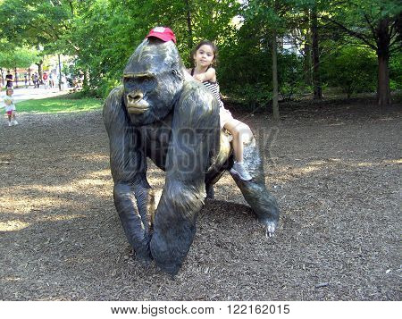 BROOKFIELD, ILLINOIS / UNITED STATES - JULY 28, 2008: A girl sits on the back of a bronze sculpture of Samson, a male silverback gorilla who was a popular attraction at the Brookfield Zoo during the 1980s.
