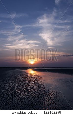 Beautiful, colorful sunrise reflects itself on the tidal waters and rippled sands of the Isle of Palms near Charleston, South Carolina