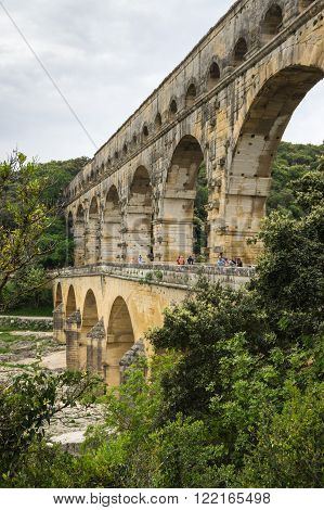 NIMES, FRANCE - MAY 04, 2015: Pont du Gard in Provence France over the Gardon river is an 160 foot high roman aqueduct built to provide water to the city of Nimes from the river Eure near Uzes in the first century A.D.