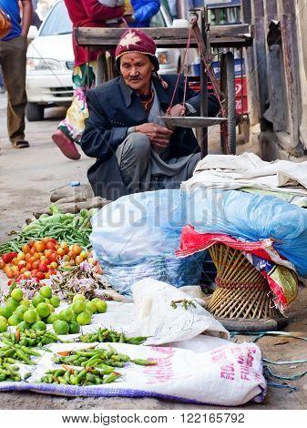 KATHMANDU NEPAL - CIRCA APRIL 2014: The street vendor sels his fruits and vegetables in Thamel in Kathmandu Nepal.