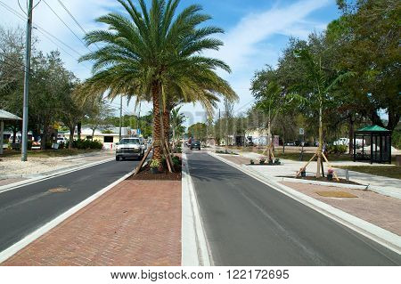 View of Old 41 Road in Bonita Springs Florida from the median showing single lane traffic and palm trees.