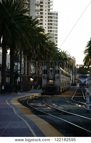 Railway tracks and a train station in downtown San Diego with two oncoming passenger trains.