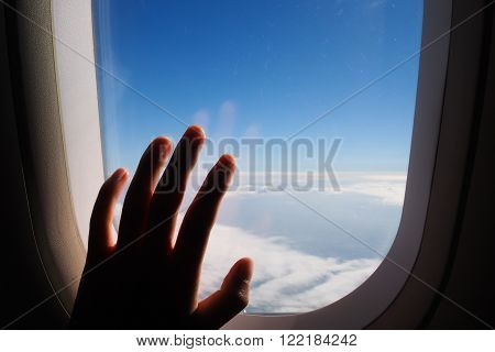 Silhouette of woman hand over the window of airplane. Clouds and sky as seen through window of an aircraft air plane.