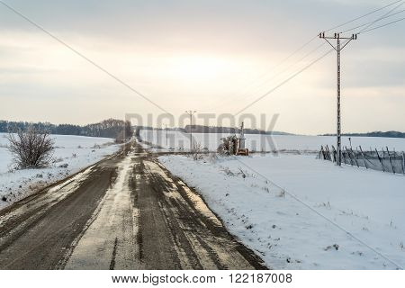 Sunset above old powerlines on the field in winter season