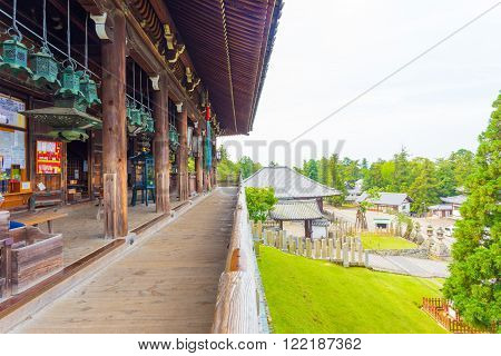NARA, JAPAN - JUNE 24, 2015: Empty wooden deck spanning front of Nigatsu-do hall overlooking the side landscape of Todai-ji temple complex in Nara Japan