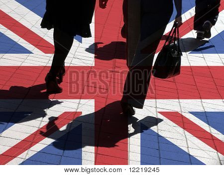 Silhouetted pedestrians overlaid onto UK flag