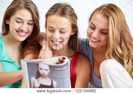 friendship, people and pajama party concept - happy friends or teenage girls reading magazine at home poster