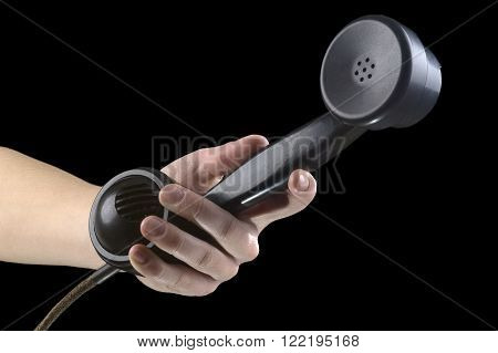 hand submits old phone handset on a black background