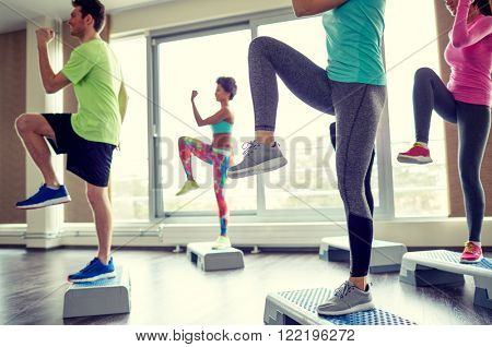fitness, sport, aerobics and people concept - group of smiling people working out and raising legs on step platforms in gym