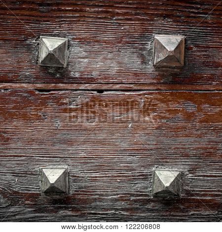 Extreme close-up of woden door of a castle with four iron nails.