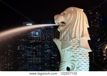 Singapore, Singapore - May 18, 2015: The Merlion statue in front of Singapore skyline at night. The Merlion is a traditional creature in Singapore with a lions head and a body of fish.
