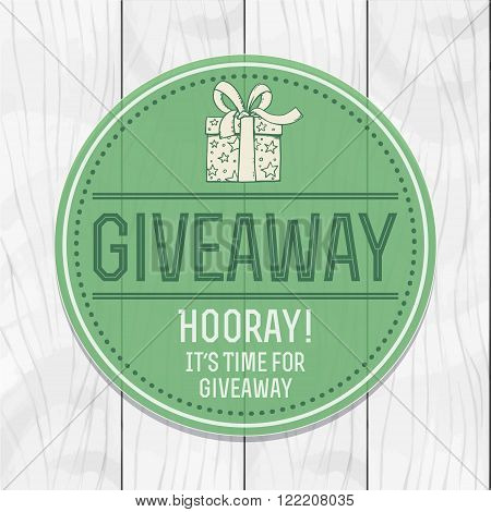 Giveaway. Advertising campaign for social networks print and other media. Round tag with uhorom and draw gift and heart. Against the background of a gray board.
