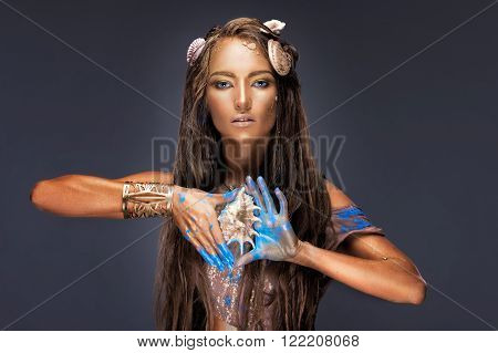 Art summer fashion portrait of beautiful girl model woman lady with art makeup golden shiny skin blue paint fingers seashells holding a shell in hand girl mermaid studio background