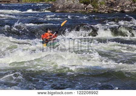 Kayaker in the  whitewater of a river Umba in Russia