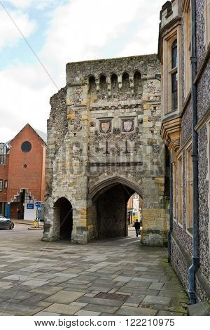 Distant person walking on stone street through arch at old medieval building in Winchester, United Kingdom