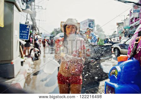 KO SAMUI, THAILAND - APRIL 13: Unidentified girl shooting water at the camera in a water fight festival or Songkran Festival (Thai New Year) on April 13, 2014 in Chaweng Main Road, Ko Samui island, Thailand.