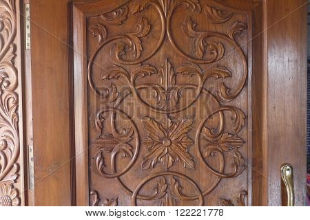 openwork carved wooden door of a case with a vegetable ornament