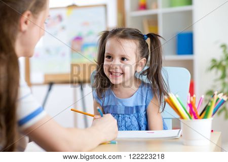 Young woman or mother teaches child to pencil in daycare. Early education in preschool, kindergarten or home.