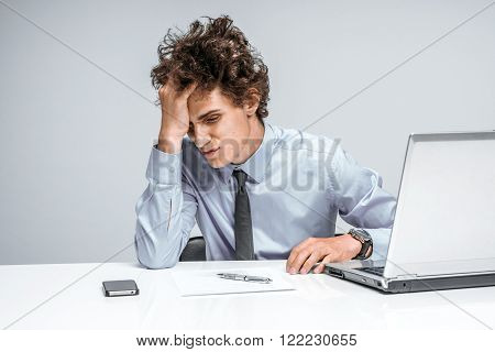 Entrepreneur dissatisfied with his earnings profit income gain benefit margin. Modern businessman at the workplace working with computer depression and crisis concept